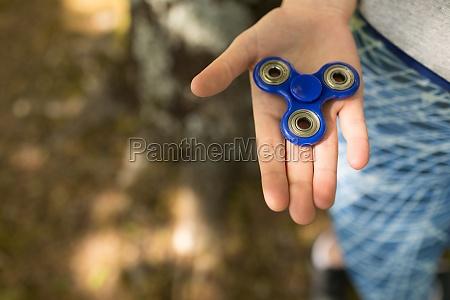 girl holding a fidget spinner in