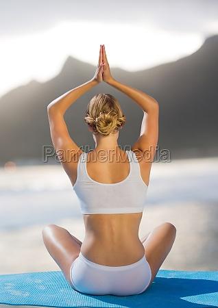 back of woman meditating on beach