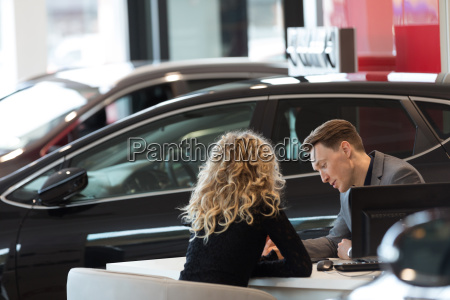 car salesperson discussing with customer in
