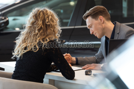 car salesperson talking with customer in