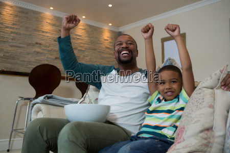 excited father and son watching football