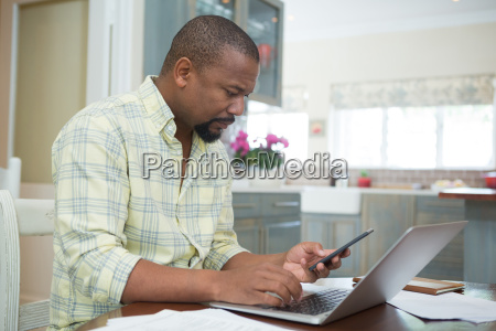 man using laptop and mobile phone