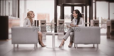 businesswomen sitting in armchair and having