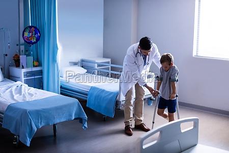 doctor assisting injured boy to walk