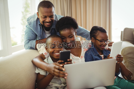 parents and kids using laptop smartphone
