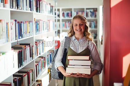 portrait of schoolgirl standing with stack