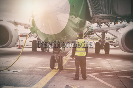 mechanic standing by airplane at runway