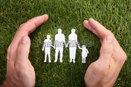 human hand protecting family paper cut
