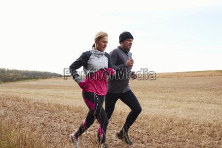 mature couple running around autumn field