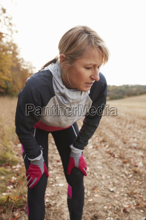mature female runner pausing for breath