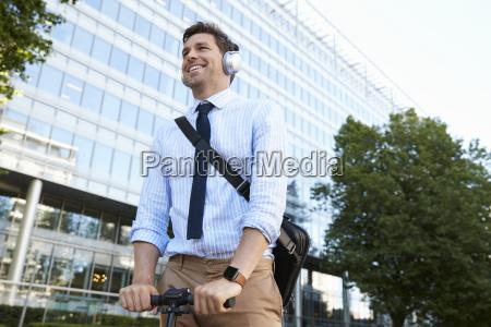 businessman wearing headphones commuting to work