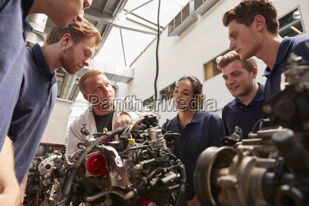 mechanic showing engines to apprentices low