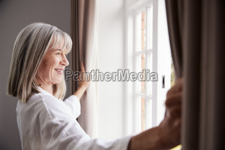 senior woman opening bedroom curtains and