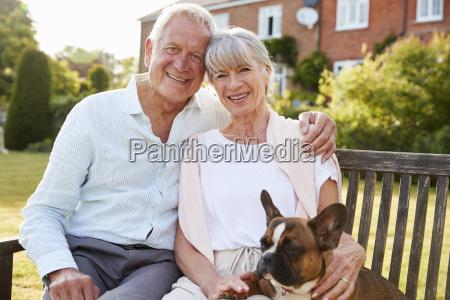 senior couple sitting on garden bench