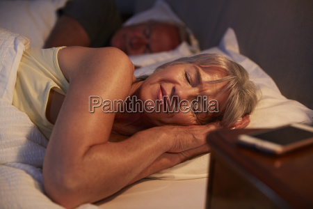 peaceful senior woman asleep in bed