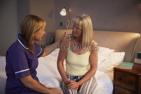 nurse talking with senior woman in