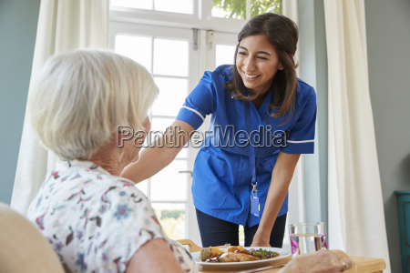 care nurse serving dinner to a