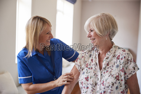 nurse helping senior woman use a