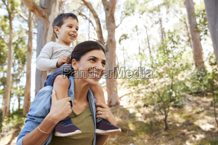 son riding on mothers shoulders on