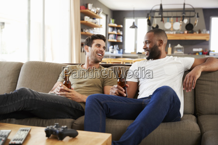 two male friends sit on sofa
