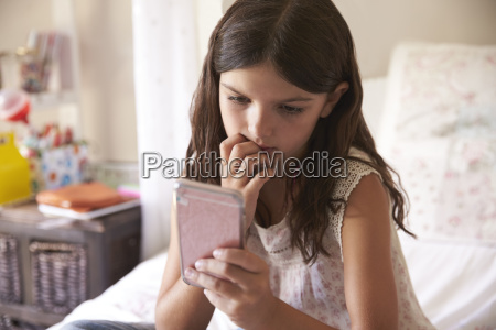 young girl in bedroom worried by