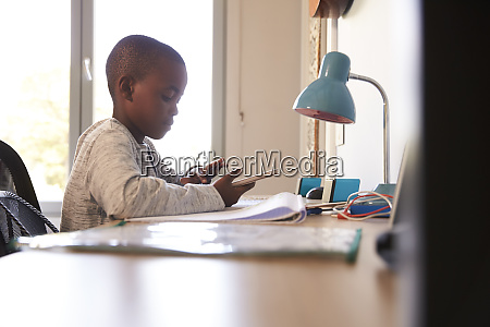 boy in bedroom using digital tablet