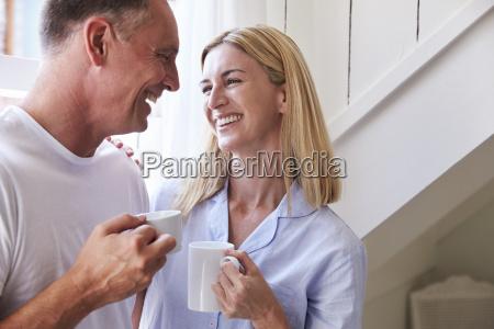 mature couple standing by bedroom window