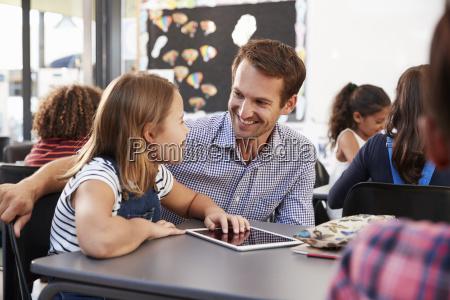 teacher and schoolgirl using tablet looking