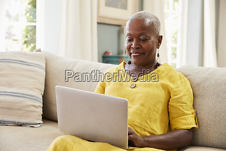 senior woman sitting on sofa using
