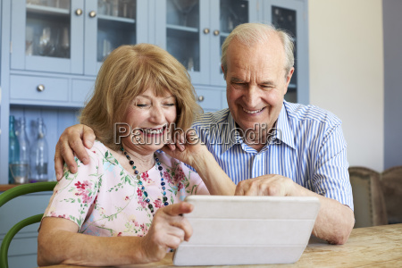 senior couple sit at home using