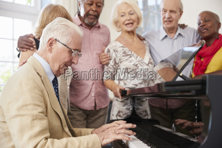 group of seniors standing by piano