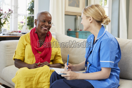 female community nurse visits senior woman