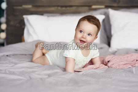 happy baby lying on bed at