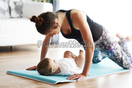 mother with baby exercising on yoga