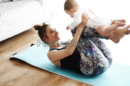 mother and baby exercising on yoga