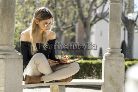 young woman with notebook sitting on