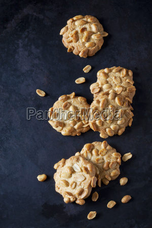 six peanut cookies on dark metal