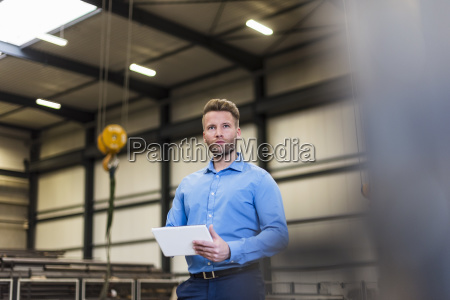 man with tablet on factory shop