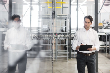 man with clipboard taking notes in
