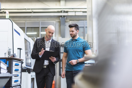 businessman and employee with clipboard in