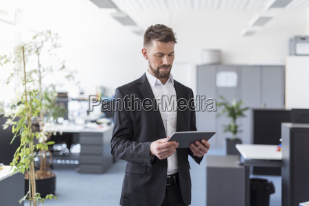 successful businessman standing in office using