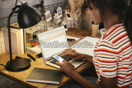 woman sitting at desk using smartphone