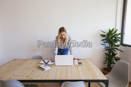 young businesswoman standing at desk using