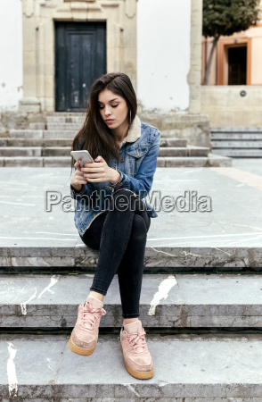 young woman sitting on stairs in