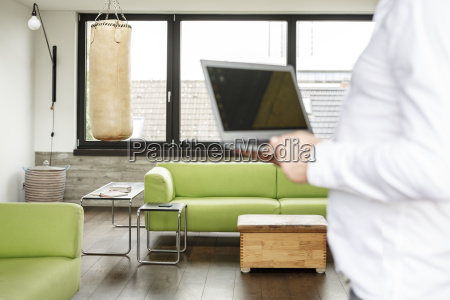 businessman holding laptop punch bag in
