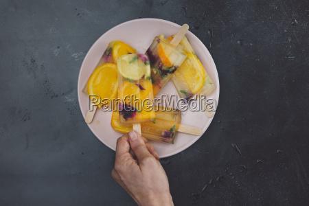 hand taking homemade orange lemon popsicle