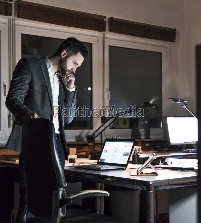 businessman standing in office at night