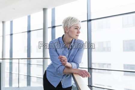 woman in office building leaning on