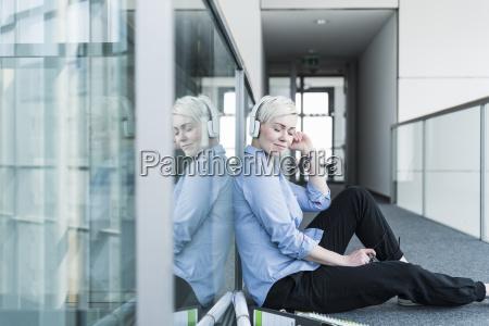 woman sitting on office floor listening