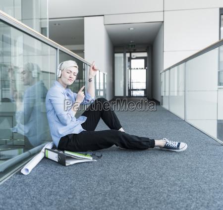 woman sitting on office floor enjoying